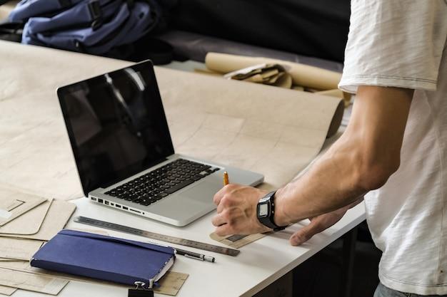 Diseñador de bienes de consumo en el trabajo en taller. manos de un hombre joven con lápiz, papel borrador y computadora portátil en una mesa de trabajo de pequeñas instalaciones de fabricación u oficina