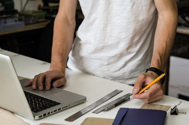 Diseñador de bienes de consumo en el trabajo en taller. manos del joven varón con lápiz y computadora portátil en una mesa de trabajo de pequeñas instalaciones de fabricación u oficina