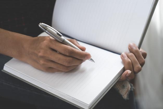 El diseñador creativo casual femenino está escribiendo la nota en el cuaderno