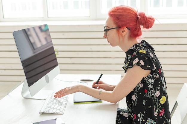 Diseñador, creativo, concepto de personas - diseñador de mujer de pelo rojo haciendo un proyecto en una tableta gráfica