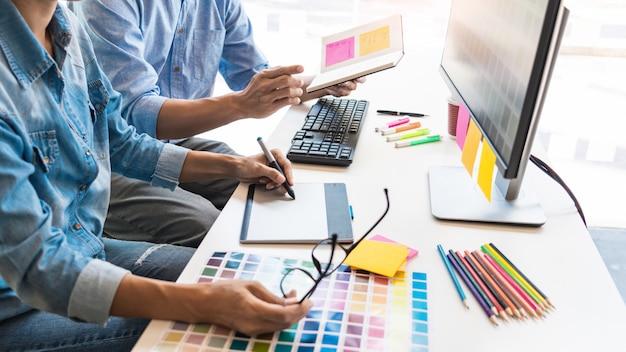 Diseñador creativo creativo gráfico trabajando juntos para colorear usando tableta gráfica y un lápiz en el escritorio con un colega.