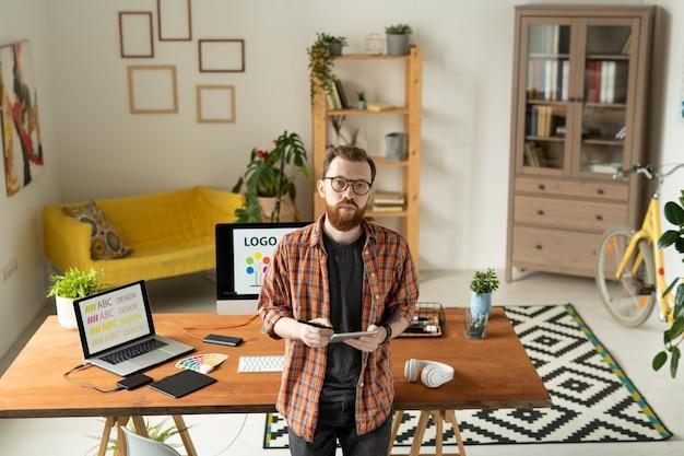 Diseñador creativo serio de pie junto a la mesa frente a la cámara y mirándote en el fondo de la computadora portátil y el monitor de la computadora con el logo