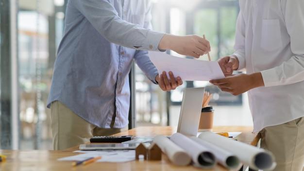El diseñador está dando consejos sobre los planos de la casa a los propietarios, los planos de la casa y el equipo colocado en la mesa de dibujo de la oficina.