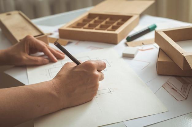 El diseñador dibuja bocetos para envases de cartón.