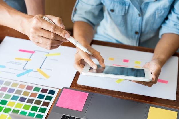 Diseñador de equipo creativo que elige muestras con desarrollo de ui / ux en diseño de boceto