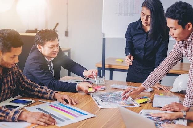 El diseñador del equipo trabaja con una gráfica de colores y una reunión de lluvia de ideas para un nuevo proyecto