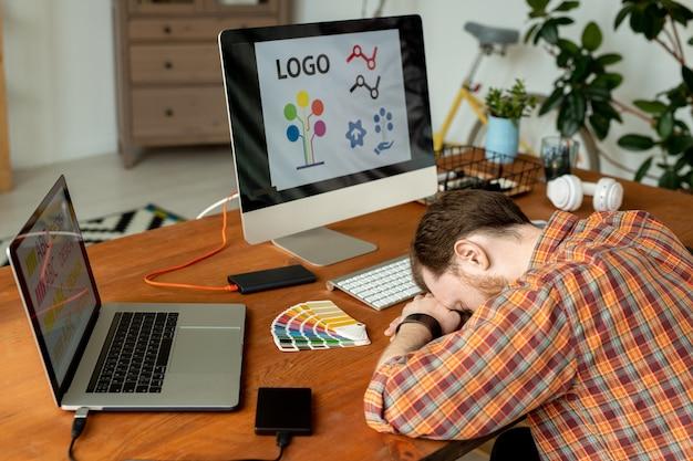 Diseñador con exceso de trabajo durmiendo en el lugar de trabajo con computadoras modernas y discos duros