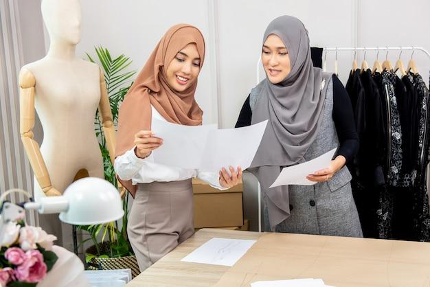 Diseñador de fasion de mujer musulmana asiática trabajando con colega