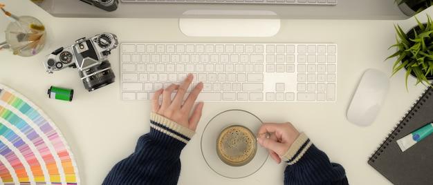 Diseñador femenino escribiendo en el teclado de la computadora y sosteniendo la taza de café en el escritorio de la oficina