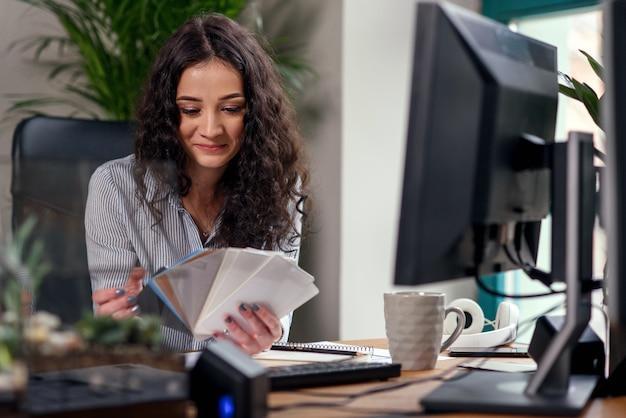 Diseñador femenino en la oficina trabajando con muestras de color. mujer en el lugar de trabajo hace una foto de la paleta de colores en el teléfono inteligente.