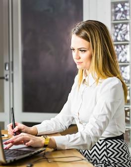 Diseñador femenino en la oficina trabajando con tableta gráfica digital y portátil. retocador de fotografía sentado en el escritorio.