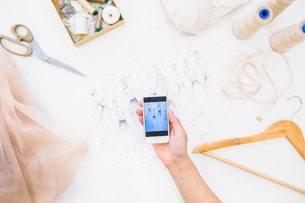 Diseñador femenino que toma la fotografía del bosquejo de la moda en teléfono inteligente