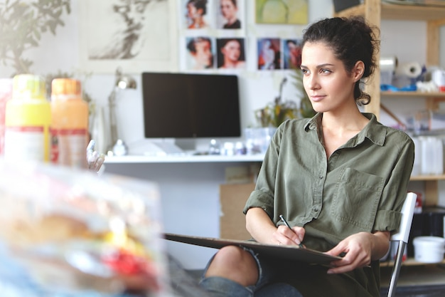 Diseñador femenino sentado en su lugar de trabajo, usando un lápiz para dibujar bocetos, mirando pensativamente a la distancia, tratando de usar su imaginación. genio talentoso mujer morena trabajando solo en el taller