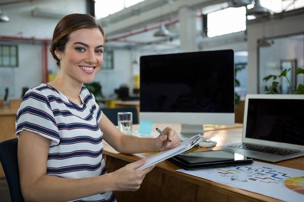 Diseñador femenino sonriente escribiendo en el portapapeles