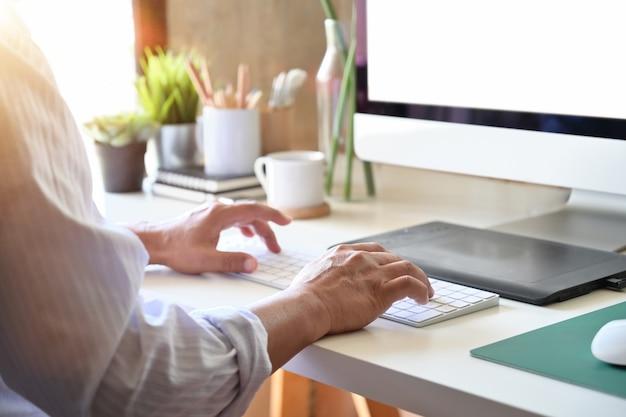 Diseñador freelance creativo trabajando con computadora y tableta digital.