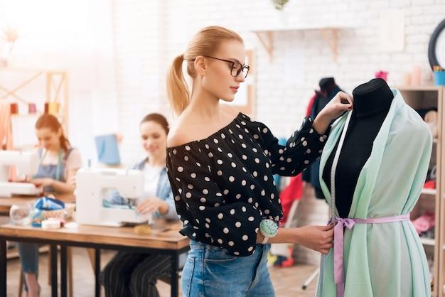 Diseñador en gafas hace medidas de vestido