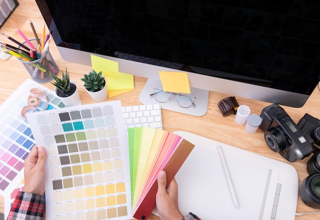 Diseñador gráfico artista creativo mirando la carta de colores en el escritorio en la oficina.