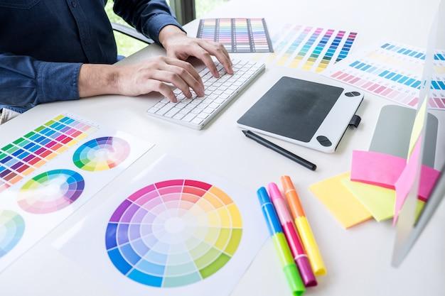 Diseñador gráfico creativo masculino que trabaja en la selección de color y muestras de color