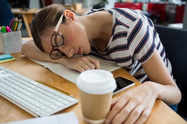 Diseñador gráfico con exceso de trabajo durmiendo en su escritorio