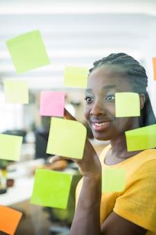 Diseñador gráfico femenina mirando notas adhesivas