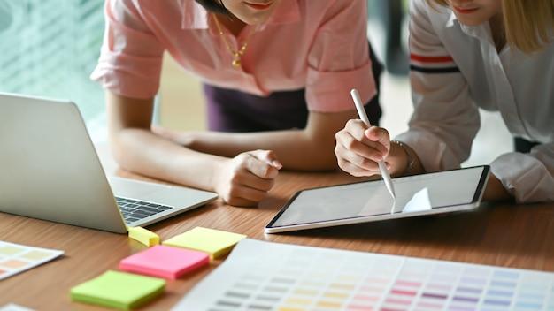 Diseñador gráfico femenino asiático trabajando juntos en la oficina usan laptop y tablet.