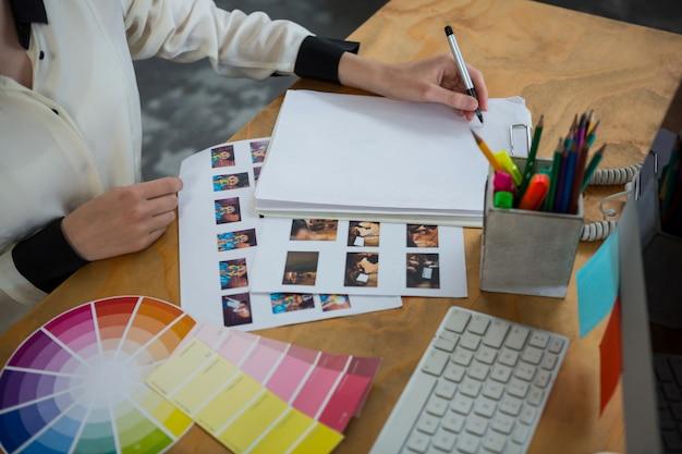 Diseñador gráfico femenino que trabaja en el escritorio