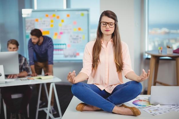 Diseñador gráfico femenino sentado en la mesa y meditando