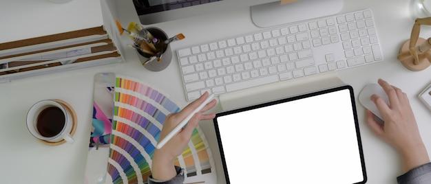 Diseñador gráfico femenino usando tableta de pantalla en blanco mientras está sentado en la mesa de trabajo con computadora y suministros