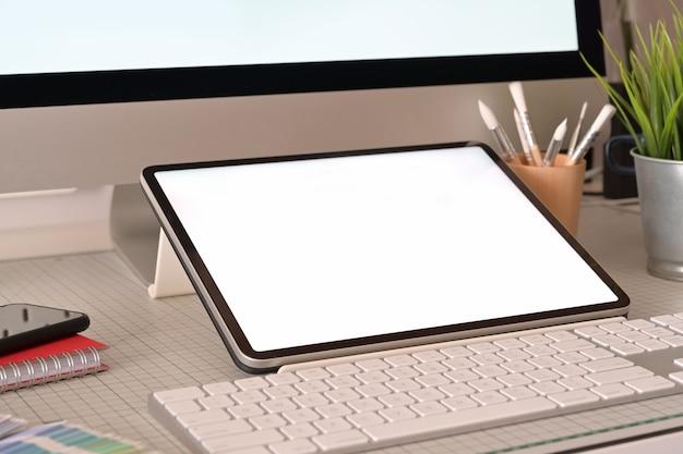 Diseñador gráfico lugar de trabajo tableta y computadora de escritorio pantalla en blanco