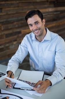 Diseñador gráfico masculino con fotos en la oficina