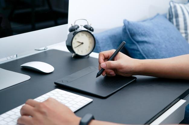 Diseñador gráfico ocupado trabajando en la computadora por el ratón pluma digital