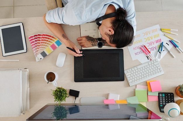 El diseñador gráfico se quedó dormido al dibujar en una tableta gráfica con un lápiz digital, vista desde arriba