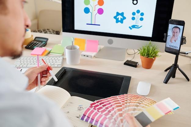 El diseñador gráfico tiene una videollamada con el cliente cuando trabaja en el logotipo de su empresa y elige el color de la paleta.