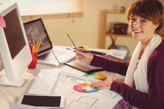 Diseñador gráfico trabajando en escritorio en oficina