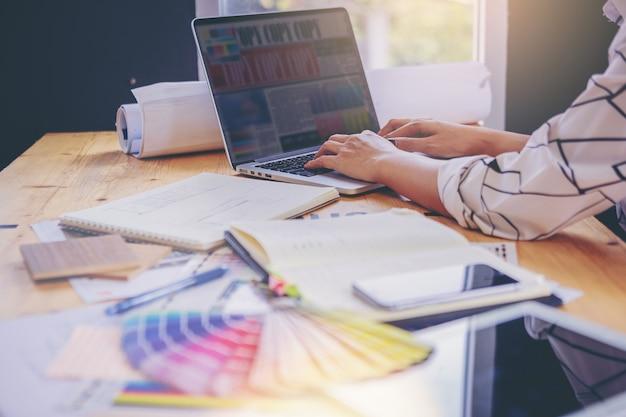 Diseñador gráfico de trabajo con carta de colores en computadora portátil para el presente proyecto de arte gráfico.