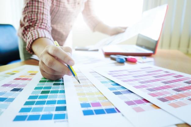 Diseñador gráfico en el trabajo. muestras de muestras de color.