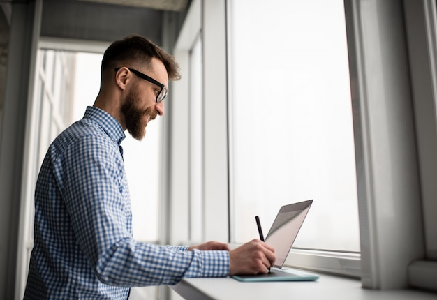 Diseñador gráfico usando laptop, tableta de dibujo digital, desarrollo de diseño para sitio web, trabajando en proyectos independientes desde casa