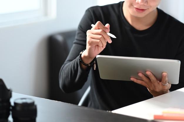 Un diseñador de hombre está utilizando un lápiz óptico y una tableta digital en su lugar de trabajo.