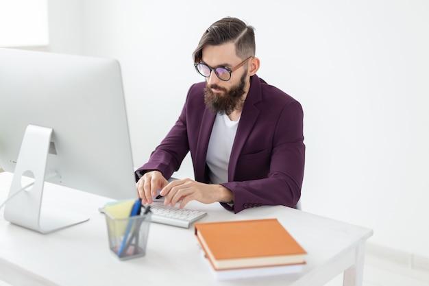 El diseñador de illustrator y el concepto de tecnología vista lateral guapo con barba trabajando en el
