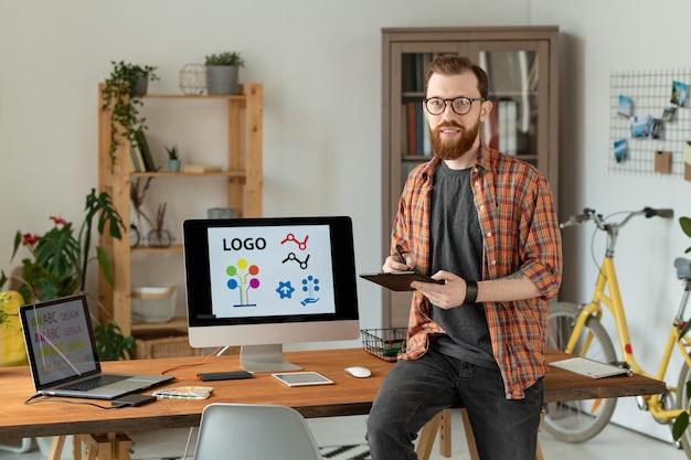 Diseñador independiente masculino alegre sosteniendo el lápiz sobre la tableta mientras está sentado en la mesa, dibujando bocetos del nuevo logotipo y mirándote con una sonrisa