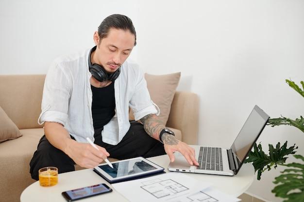 Diseñador de interiores creativo que comprueba los planos de construcción cuando trabaja en un proyecto para clinet