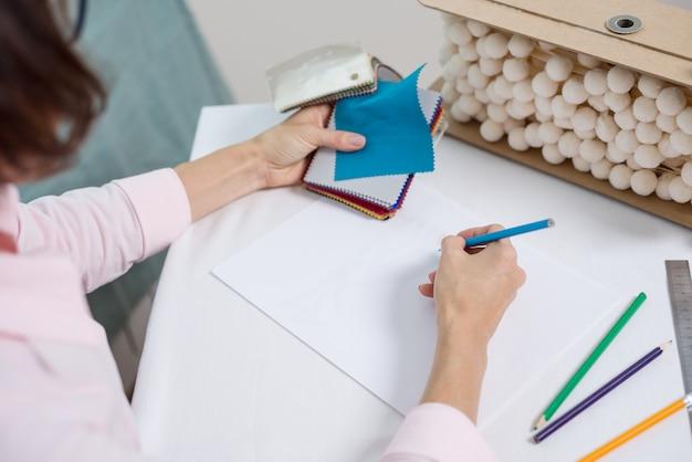 Diseñador de interiores dibuja en el escritorio de la oficina con lápiz