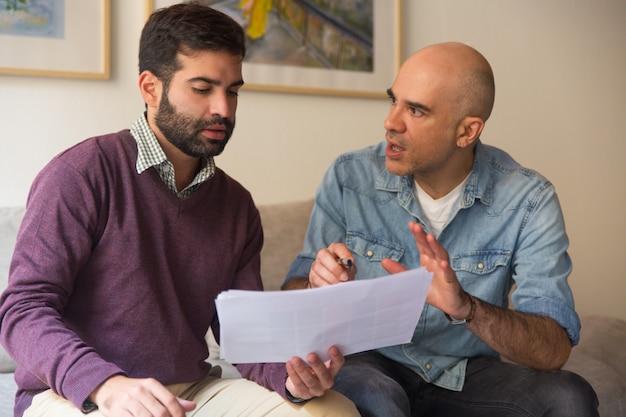Diseñador de interiores y dueño de casa discutiendo sobre bocetos