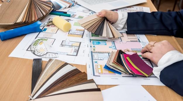 Diseñador de interiores con muestra de color y planos de construcción en la oficina.
