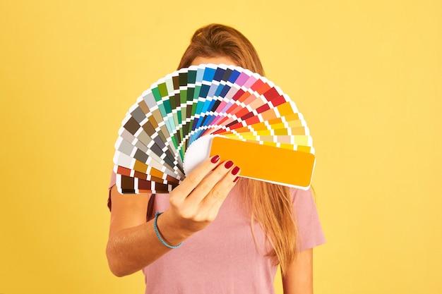 Diseñador de interiores mujer sosteniendo una paleta de guía de color aislada