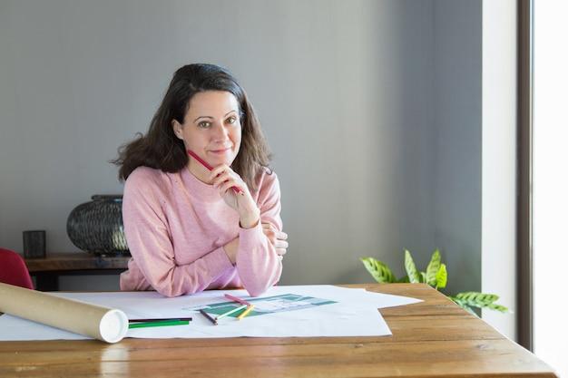 Diseñador de interiores pensativo sonriente que piensa sobre plan de la renovación