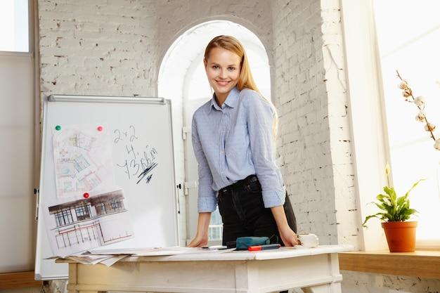 Diseñador de interiores profesional que trabaja con dibujos de habitaciones en la oficina moderna