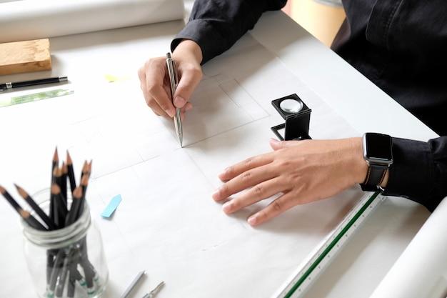 Diseñador de interiores que trabaja en los planos en el lugar de trabajo creativo del estudio.