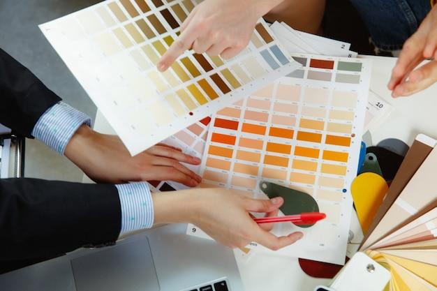Diseñador de interiores trabajando con pareja joven. familia encantadora y diseñador o arquitecto profesional discutiendo el concepto del futuro interior, trabajando con paleta de colores, dibujos de habitaciones en la oficina moderna.