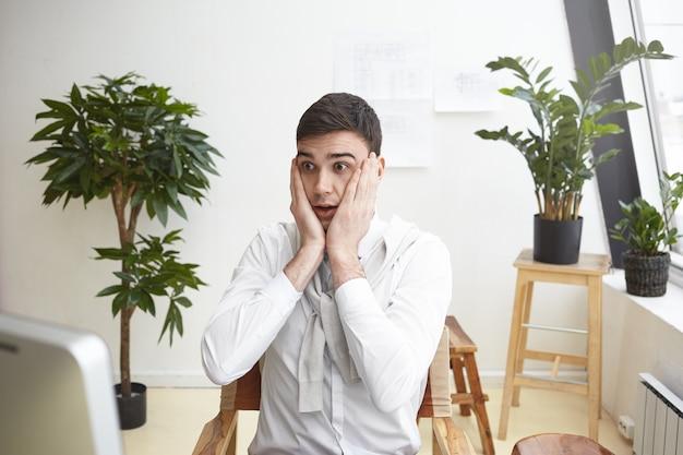 Diseñador masculino desconcertado gesticulando presa del pánico, mirando la pantalla de la computadora, con una mirada de asombro y preocupación porque no puede terminar el dibujo del plan de construcción a tiempo. plazo y estrés en el trabajo
